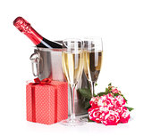 Champagne bottle, two glasses, gift box and red rose flowers