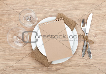 Blank paper on plate, wine glasses and silverware set