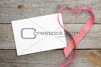 Blank valentines greeting card and red heart shaped ribbon