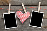 Two blank instant photos and red heart hanging on the clotheslin