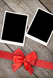 Two photo frames over wooden background with red bow