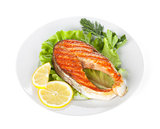 Grilled salmon with lemon slices and herbs on plate