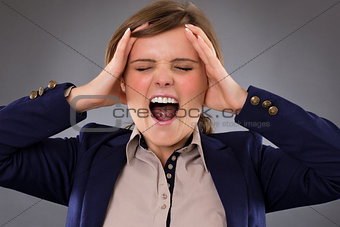 Angry businesswoman screaming and holding her head