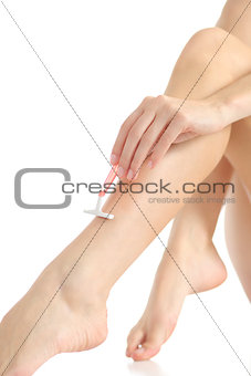 Close up of a woman hand with a shaver shaving legs