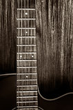 Detail of acoustic guitar in vintage style on wood background