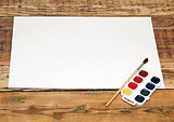 Set of used paint bruch with paper on wood background