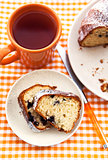 Piece of homemade bundt cake on plate with orange mug