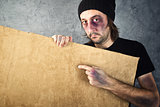 Man with bruises holding blank cardboard paper