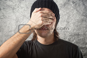 Casual Man with Black Cap covering face