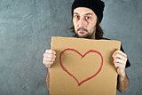 Man holding cardboard paper with heart shape drawing