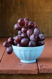 large ripe black grapes in a blue bowl