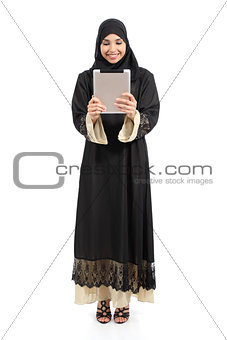 Arab saudi woman standing looking a tablet reader
