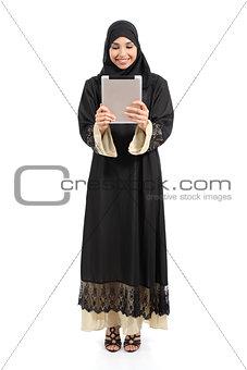 Arab saudi woman standing looking a tablet reader