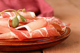 sliced ​​dried sausage meat (ham, prosciutto, salami) served on a wooden board