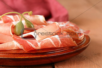 sliced dried sausage meat (ham, prosciutto, salami) served on a wooden board