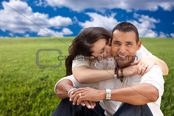 Hispanic Couple Sitting in Grass Field