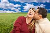 Happy Mixed Couple Sitting in Grass Field