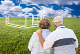 Senior Couple Standing in Grass Field Looking at Ghosted House