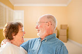 Happy Senior Couple In Room with Moving Boxes on Floor
