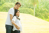 Happy young pregnant Asian couple