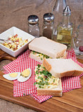 Fresh egg and bacn on white sandwich in rustic kitchen setting