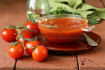 tomato soup with fresh vegetables and capers in a glass bowl