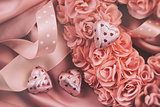Heart made of pink roses with ribbons and chocolates on satin
