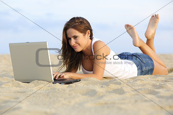 Beautiful teenager girl browsing her laptop lying on the sand of the beach