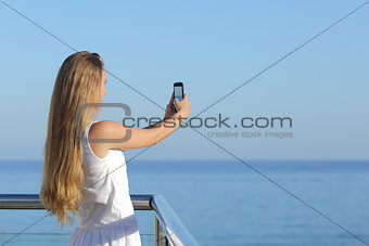 Woman making a photograph of the sea with a smart phone