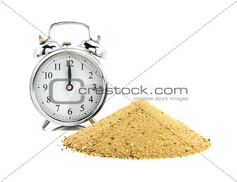 Alarm clock with pile of sand  of white background