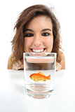 Pet fish in a glass needs care and a woman looking it