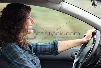 Profile of a happy woman driving a car