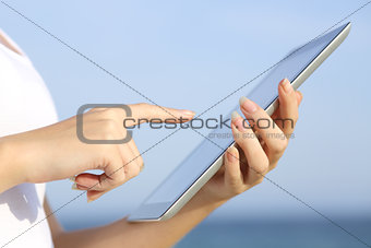 Profile of a woman hands holding and browsing a digital tablet on the beach