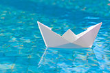 White paper boat floating in the water