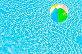 multicolored ball and turquoise water with ripples
