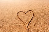 drawing a heart on the wet sand at the sea