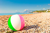 colorful inflatable ball on a pebble beach