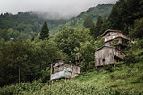 Wooden Huts and a House on a Hillside
