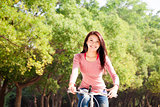 Happy young girl with bicycle outdoor portrait.