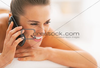 Portrait of young woman laying on massage table and talking cell