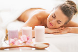 Closeup on spa therapy ingredients and relaxed young woman in ba