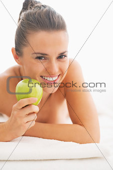 Portrait of happy young woman with apple laying on massage table