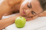 Relaxed young woman with apple laying on massage table