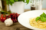 tasty fresh pasta with garlic and basil on table