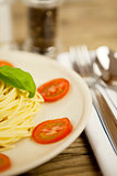 fresh tasty pasta with tomato and basil on table