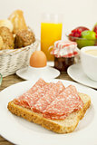 tasty breakfast with salami toast on table