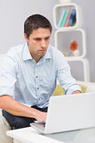 Serious man using laptop at home