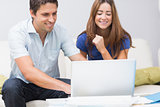 Cute couple using laptop at home