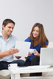 Smiling couple paying their bills online at home