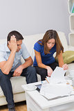 Worried couple paying their bills in living room at home